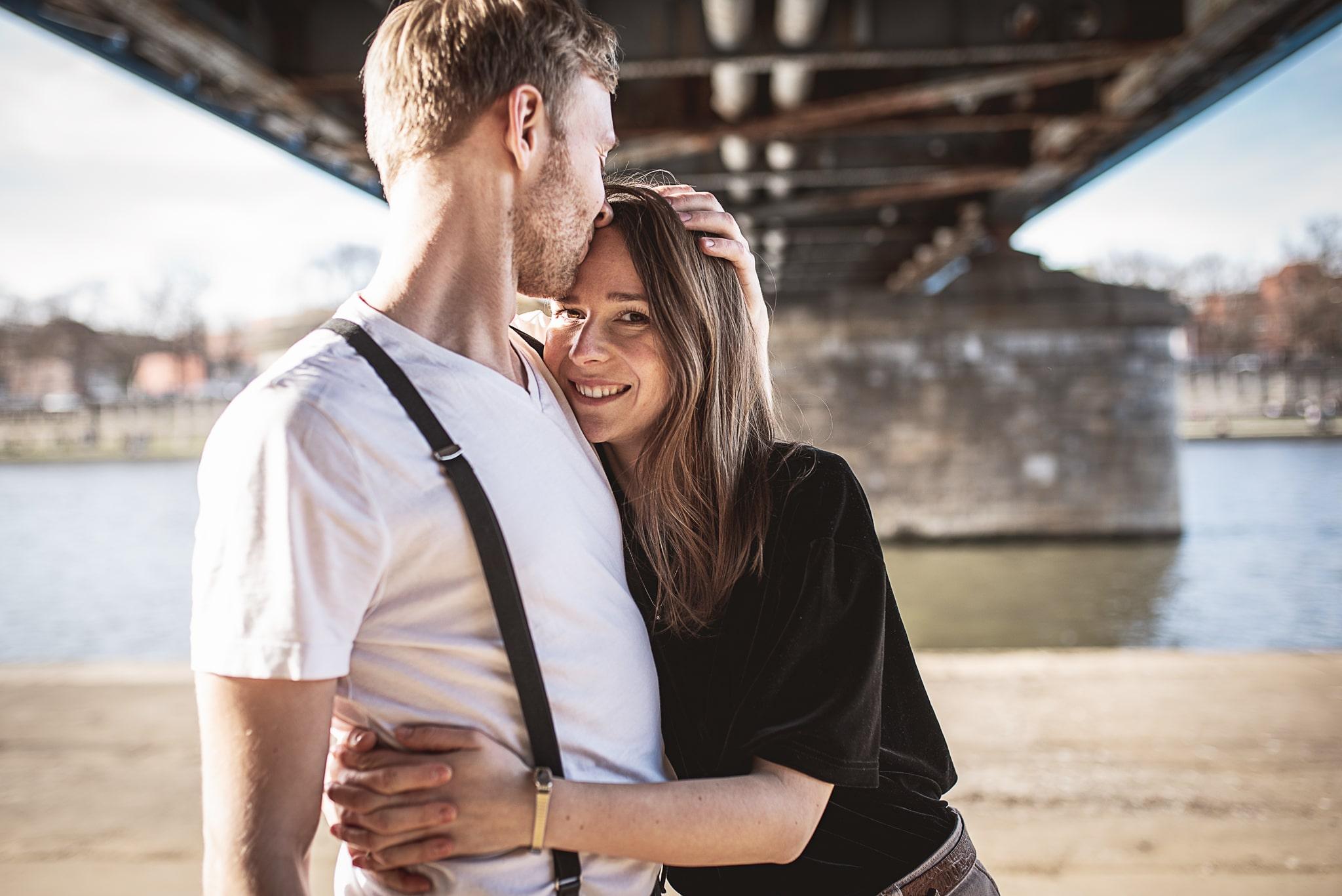 dziewczyna przytula ukochanego pod mostem