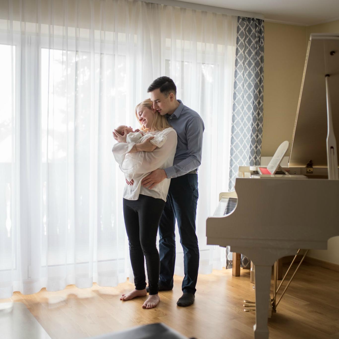Rodzice w domu przy oknie trzymają noworodka