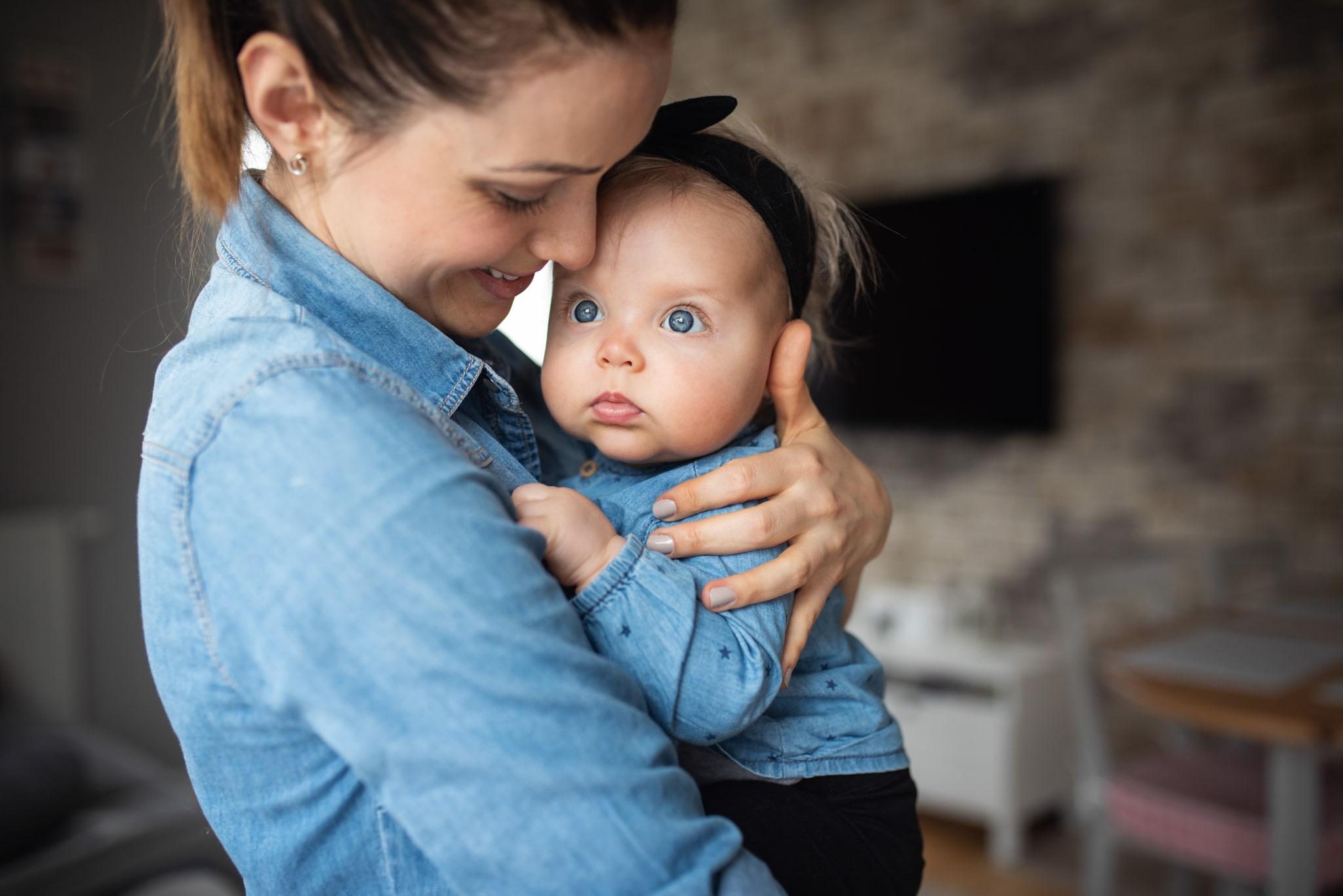 mama przytula córeczkę w domu