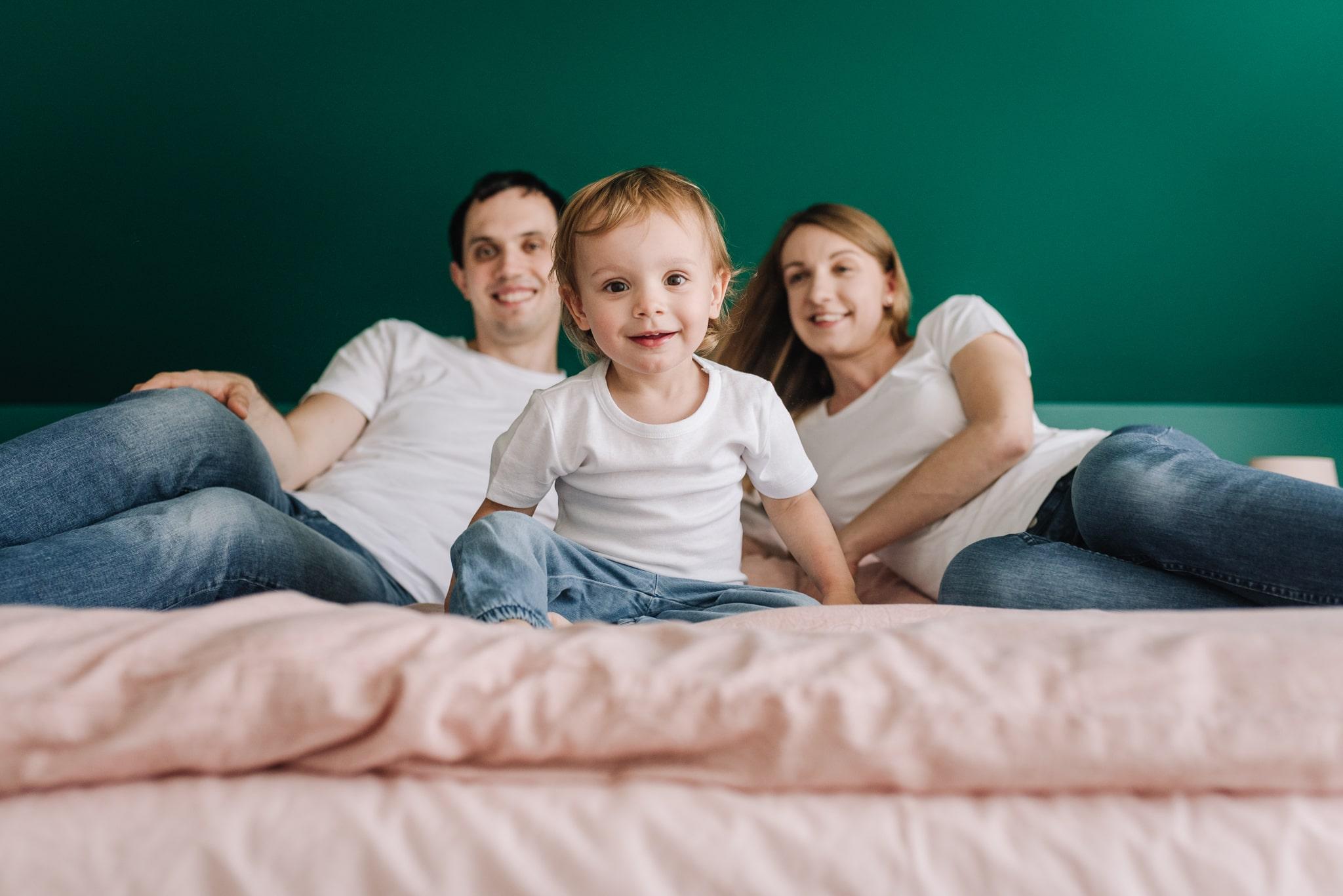 rodzice i córeczka siedzą na łóżku podczas sesji lifestyle