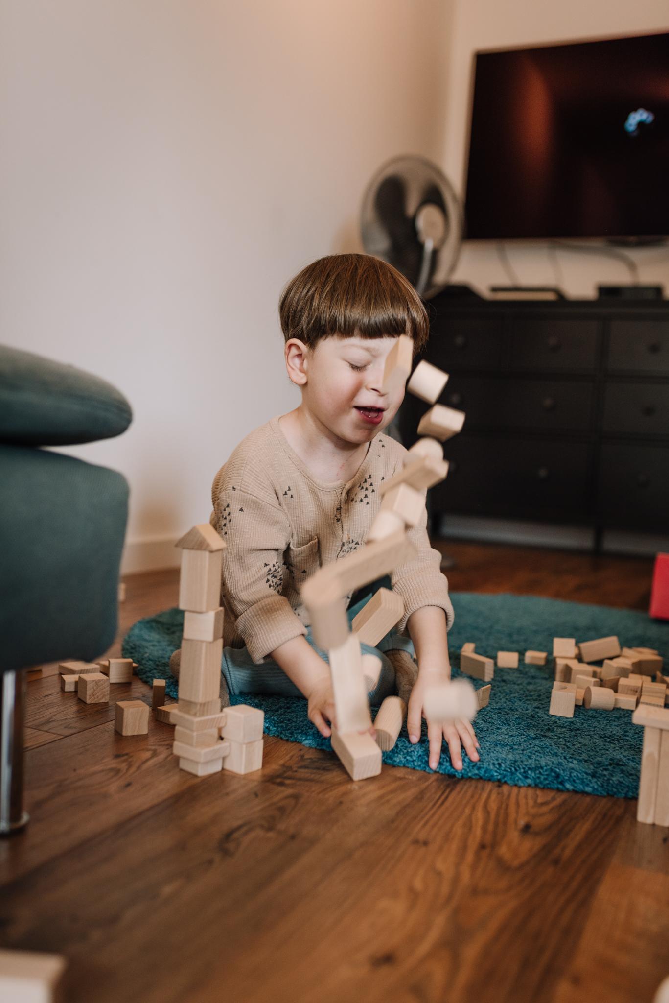 upadająca wieża z klocków drewnianych układana przez chłopca