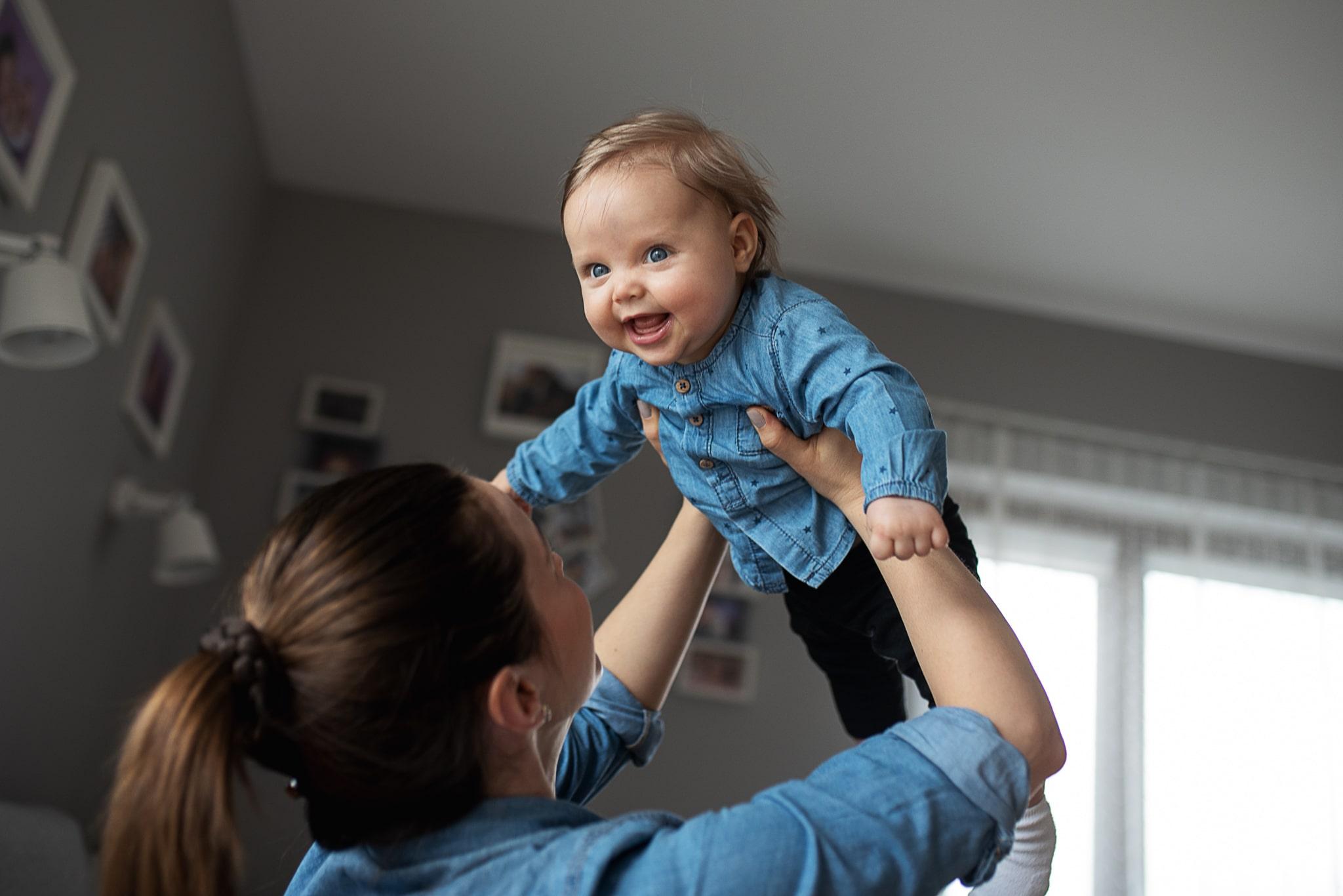 córeczka podnoszona do góry na rękach przez mamę