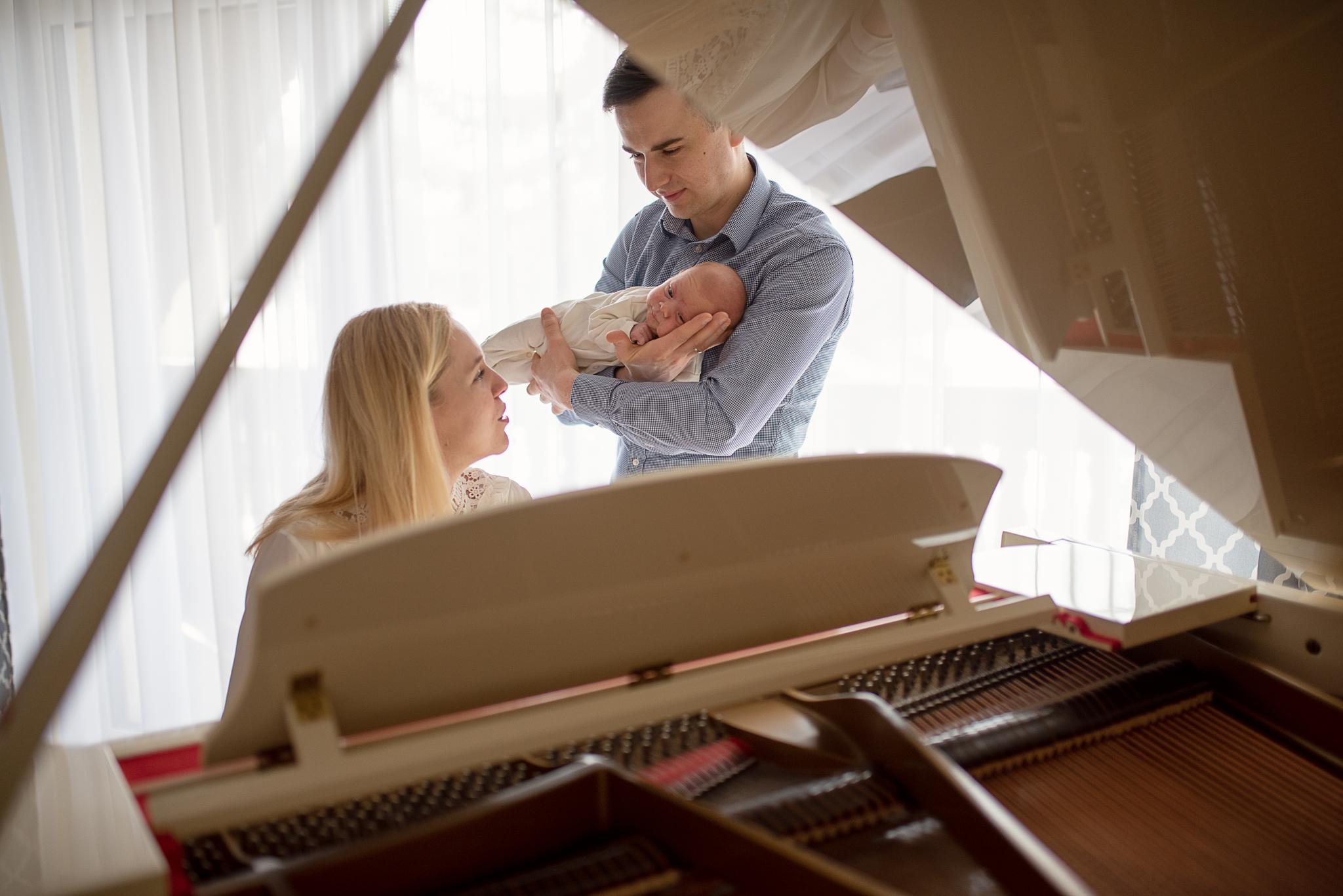 mama gra na fortepiania tata trzyma noworodka na rękach