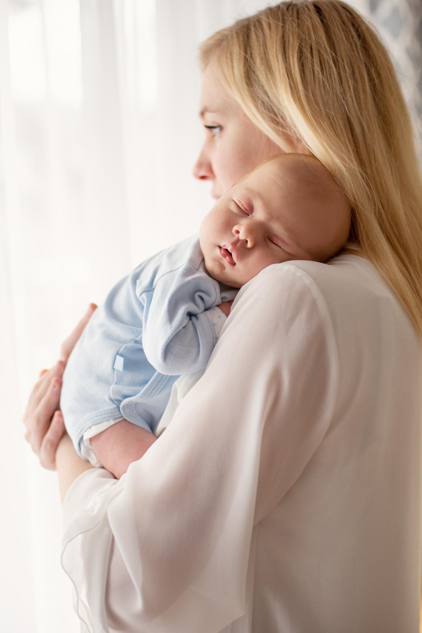 śpiący noworodek u mamy