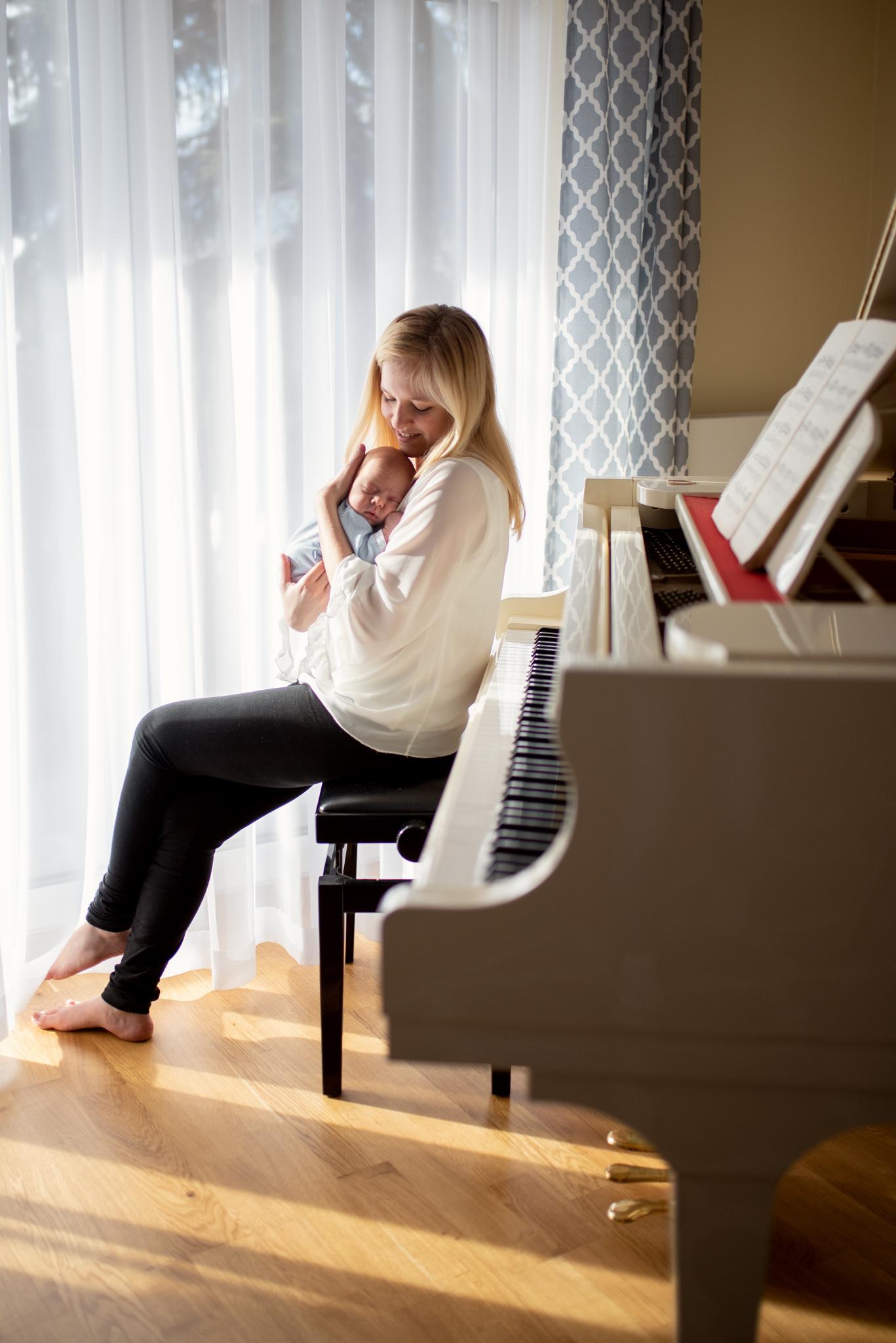 mama siedzi przy fortepianie tuląc noworodka