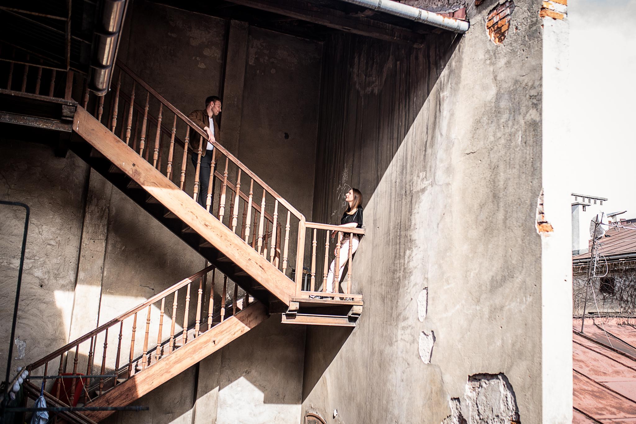 stojąca para na starych schodach w kamienicy