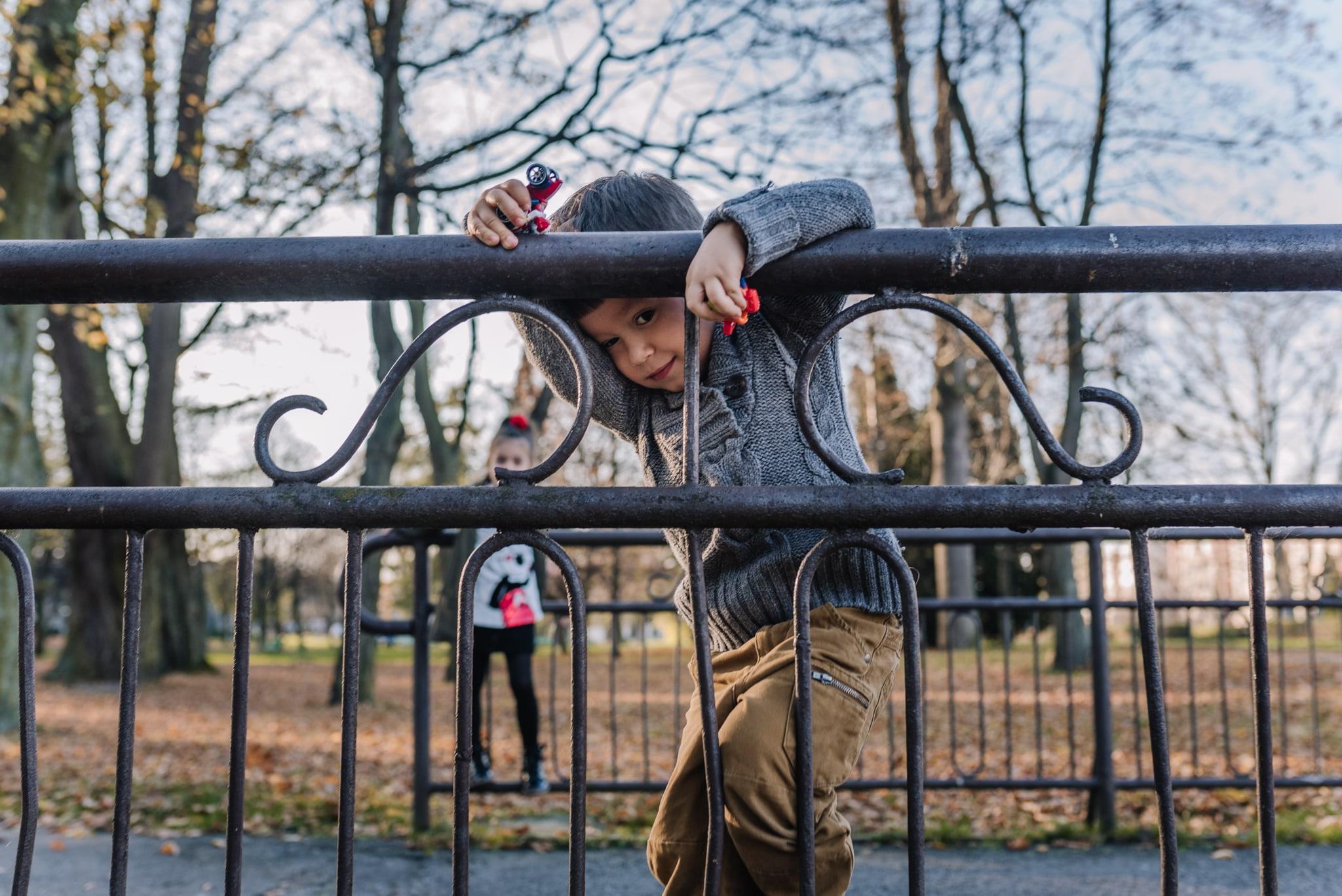 chłopczyk wspinający się na barierkę