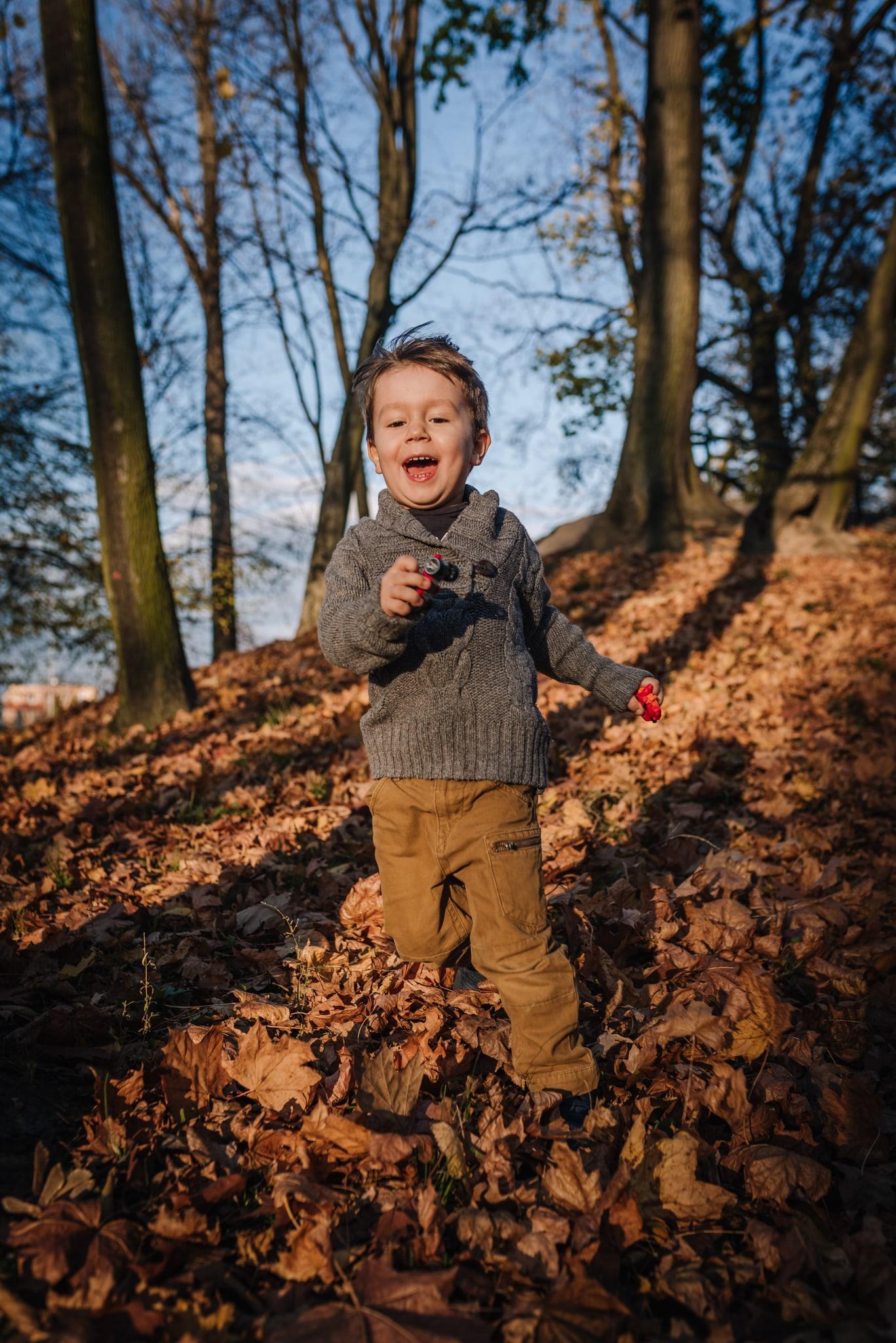 uśmiechnięty chłopczyk zbiega z górki