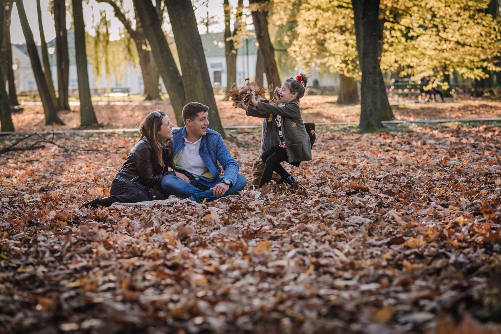 dzieci rzucają w rodziców liśćmi