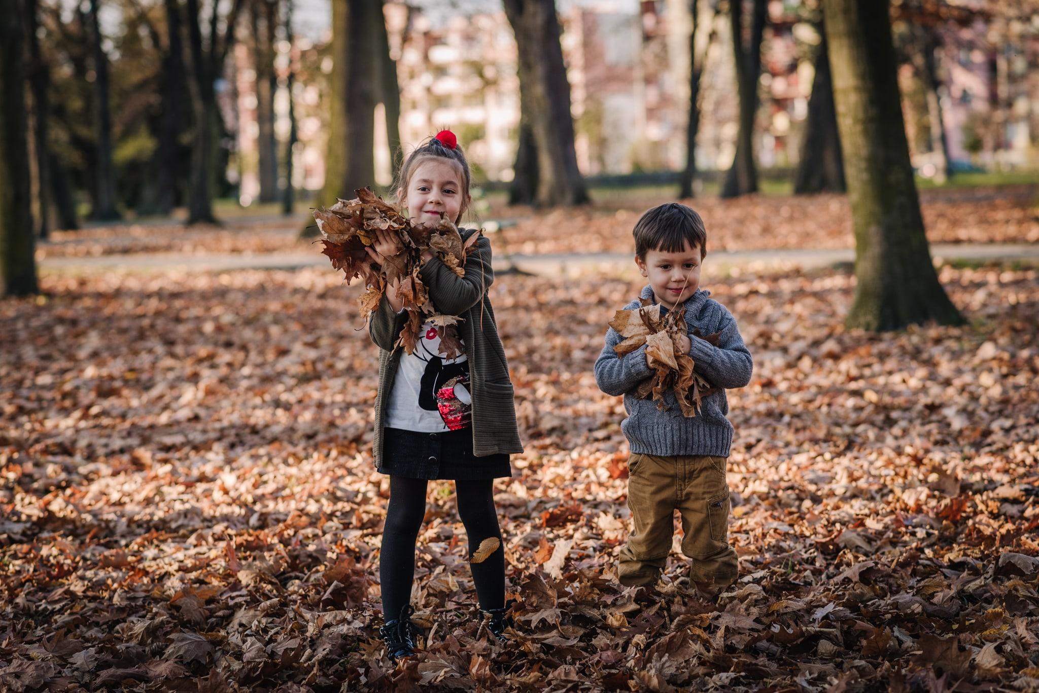 dziewczynka i chłopiec zbierają liście