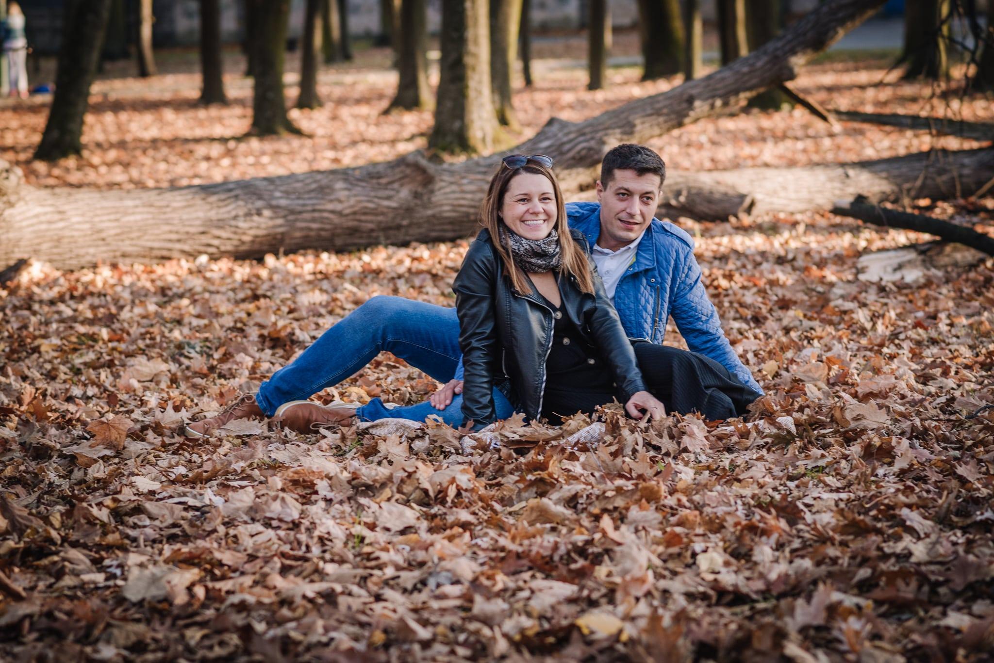 uśmiechnięci rodzice siedzący na kocu w parku
