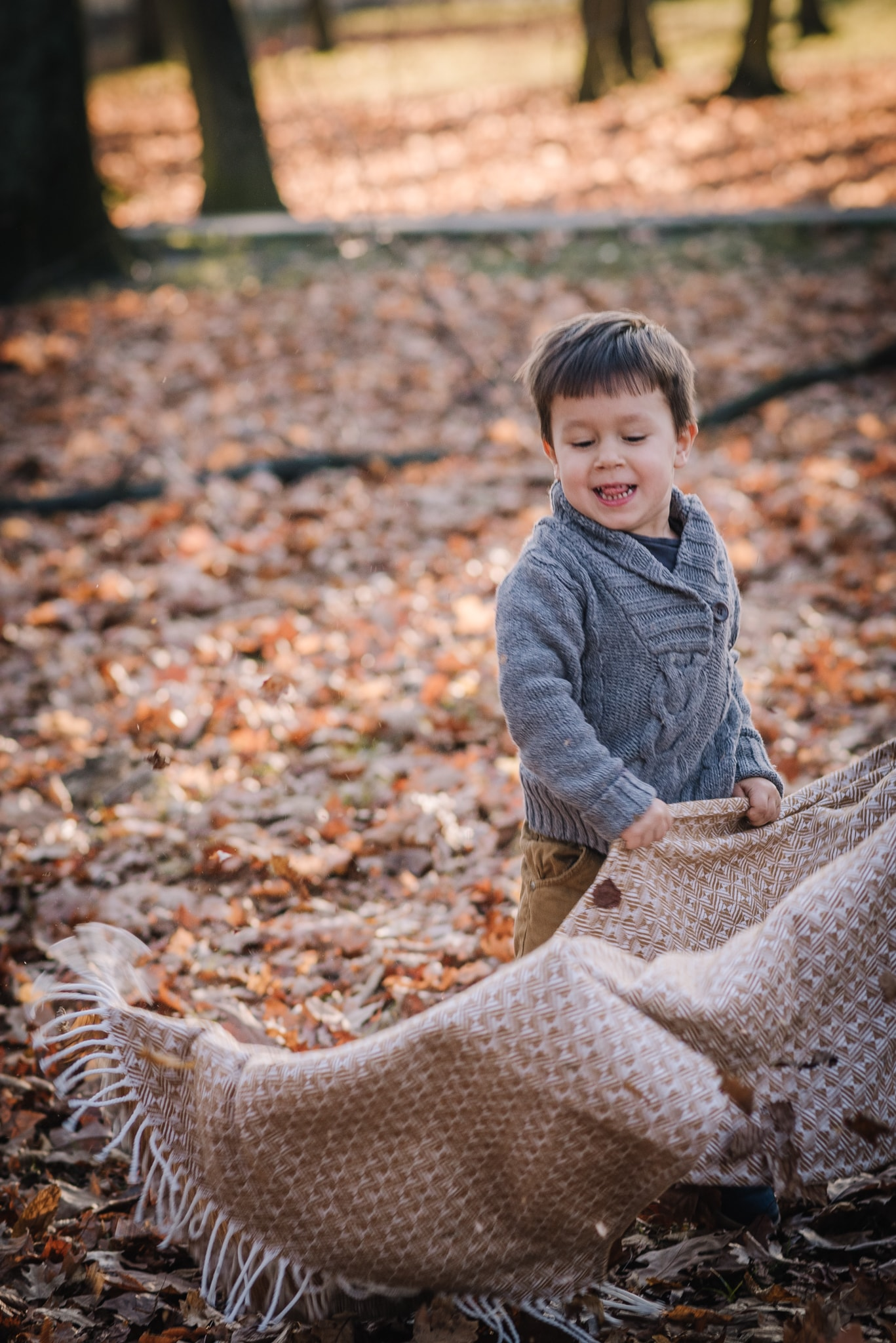 chłopczyk bawi się kocem w parku