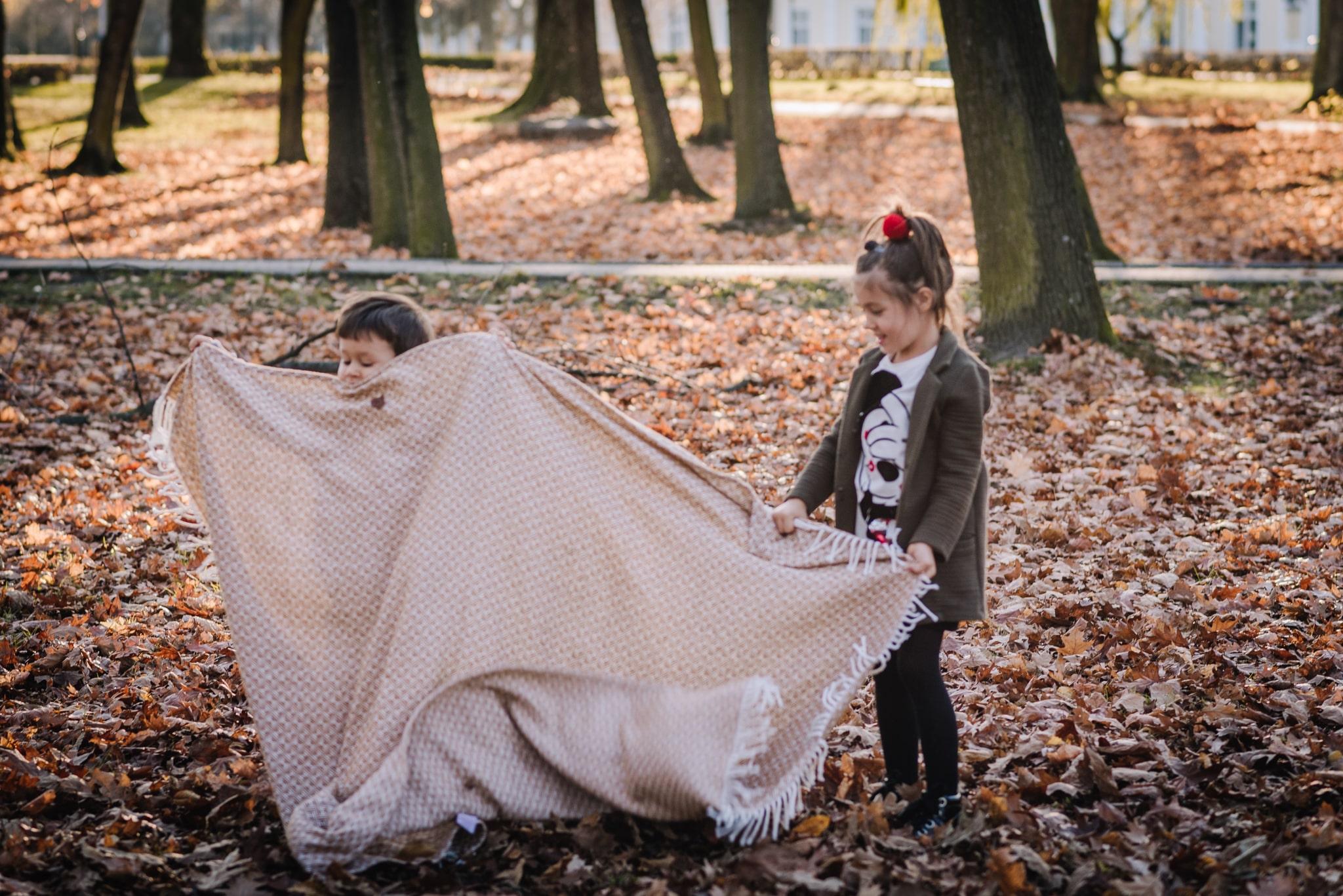 dzieci rozkładają koc w parku