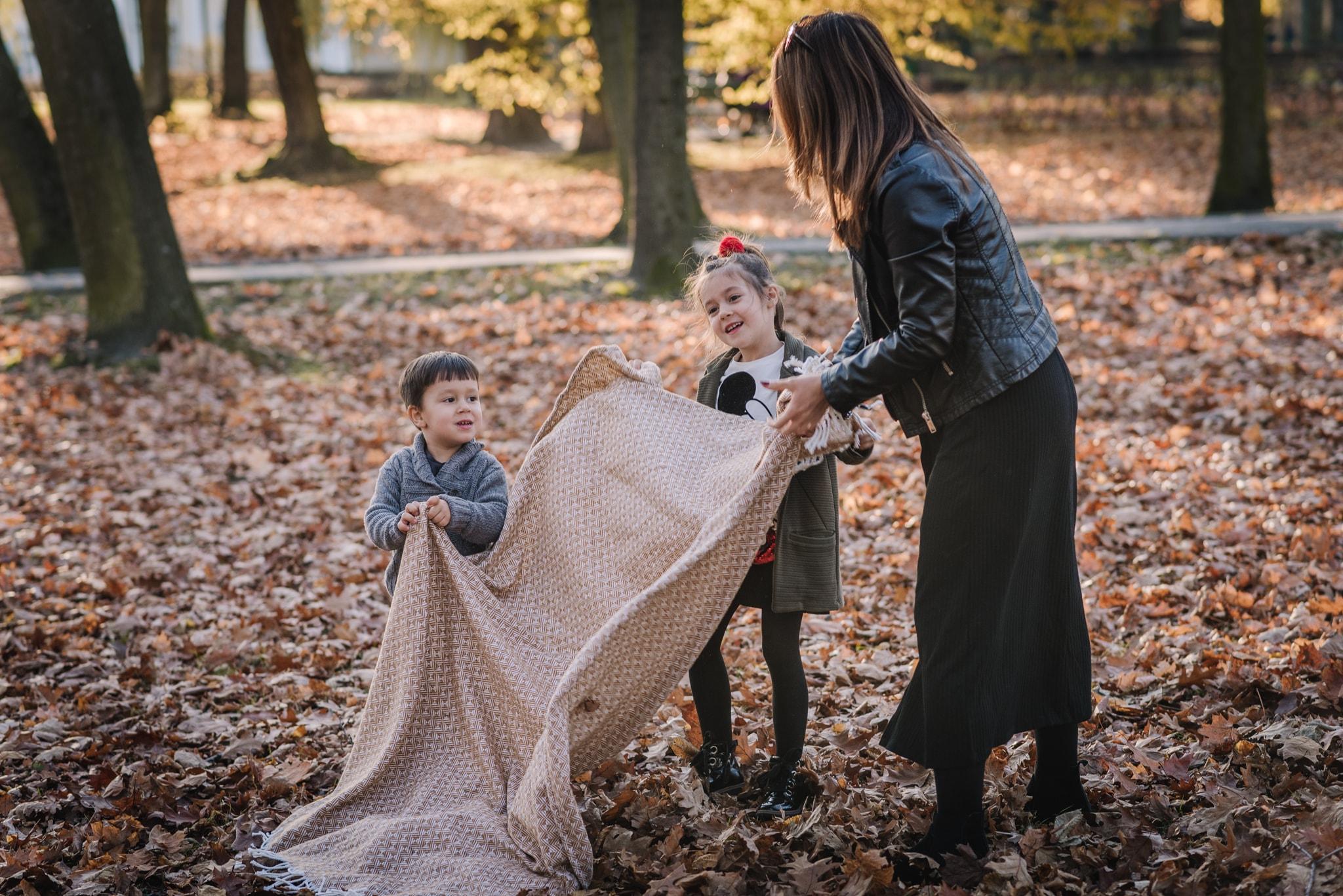 mama pomaga rozkładać dzieciom koc w parku