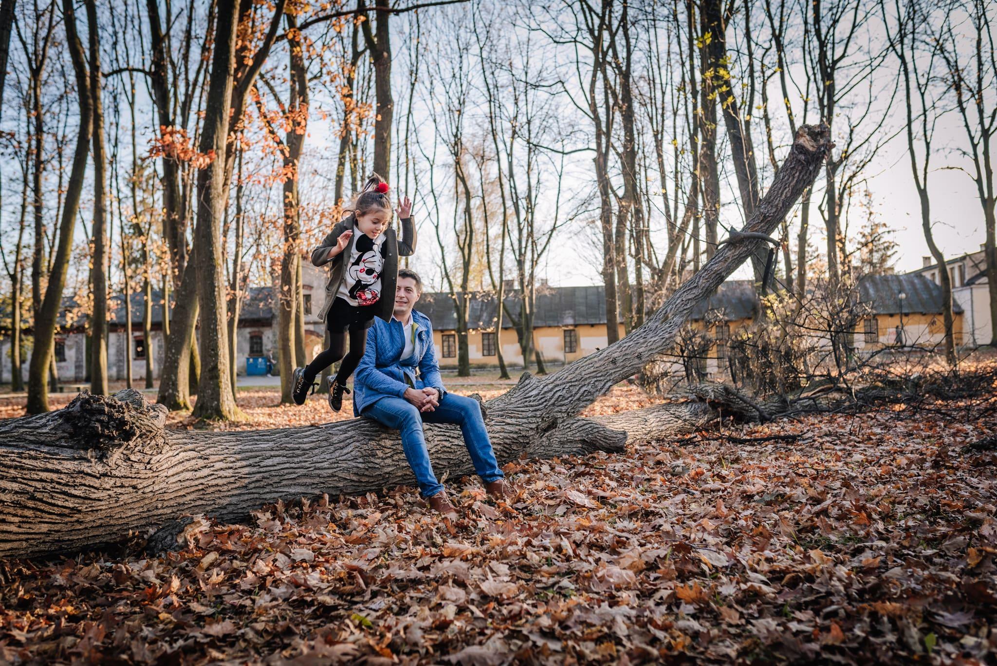 dumny tata podziwia skok córki z pnia drzewa