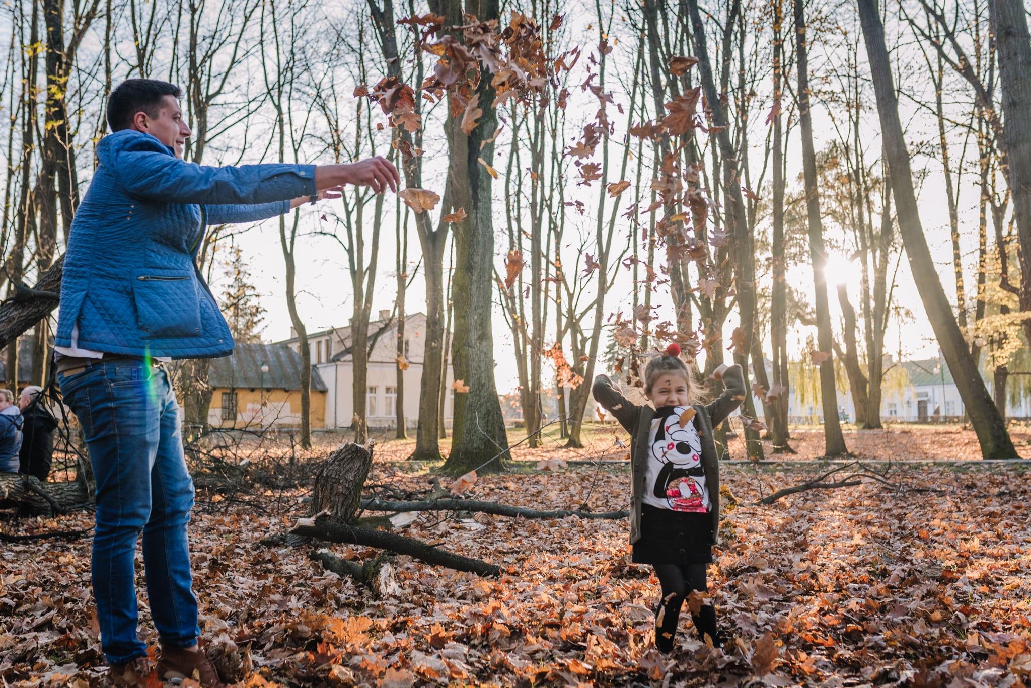 tata rzuca  w córkę liśćmi w parku jesienią