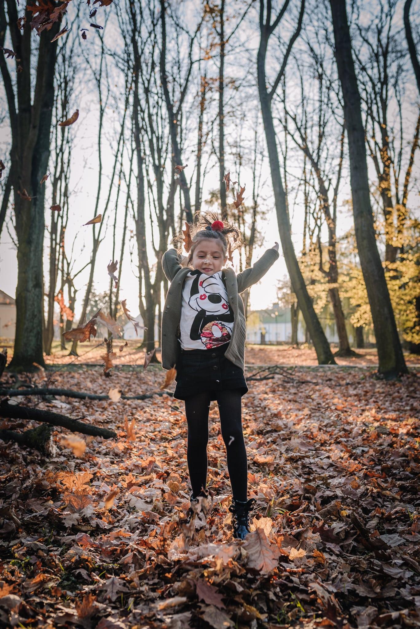 dziewczynka podrzuca liście do góry