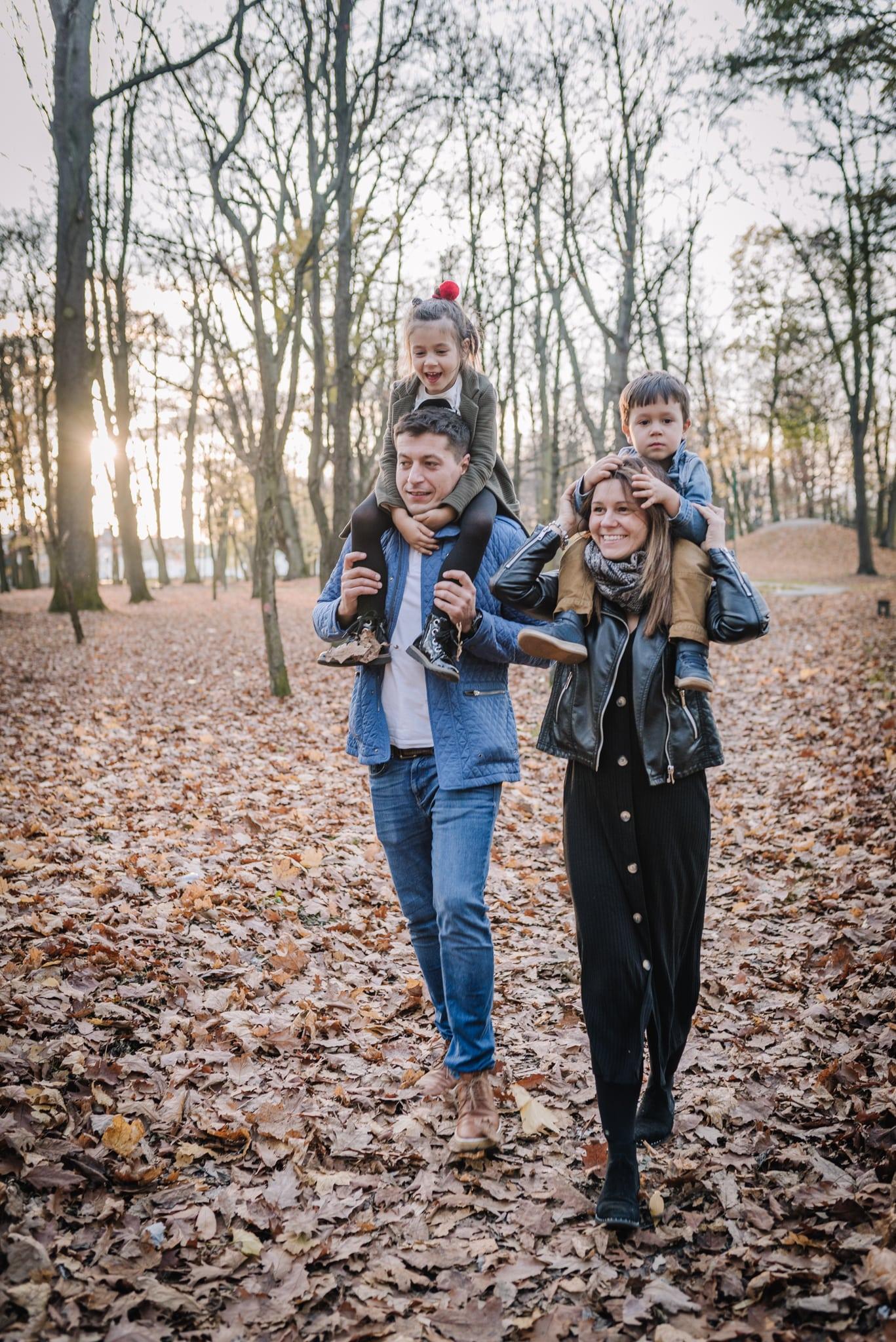 na spacerze w parku córeczka na barana u taty a synek u mamy