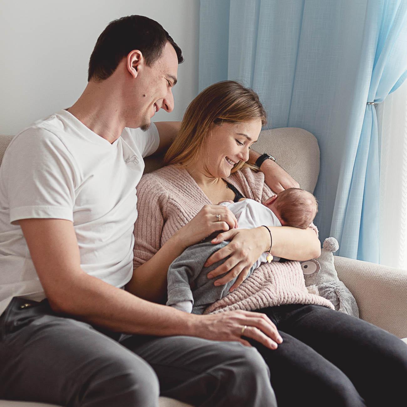 młodzi rodzice razem wtuleni podczas karmienia piersią