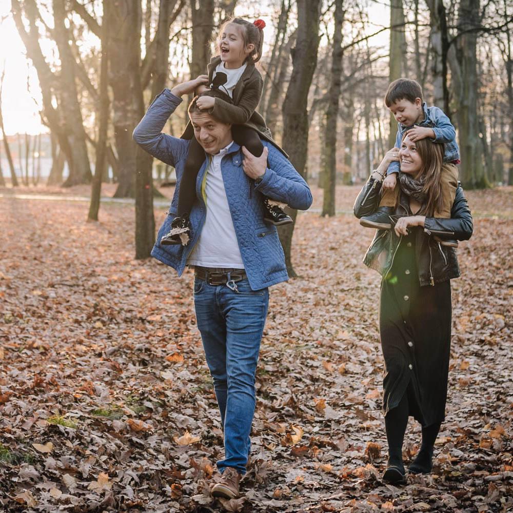 dzieci na barana u rodziców podczas jesiennego spaceru
